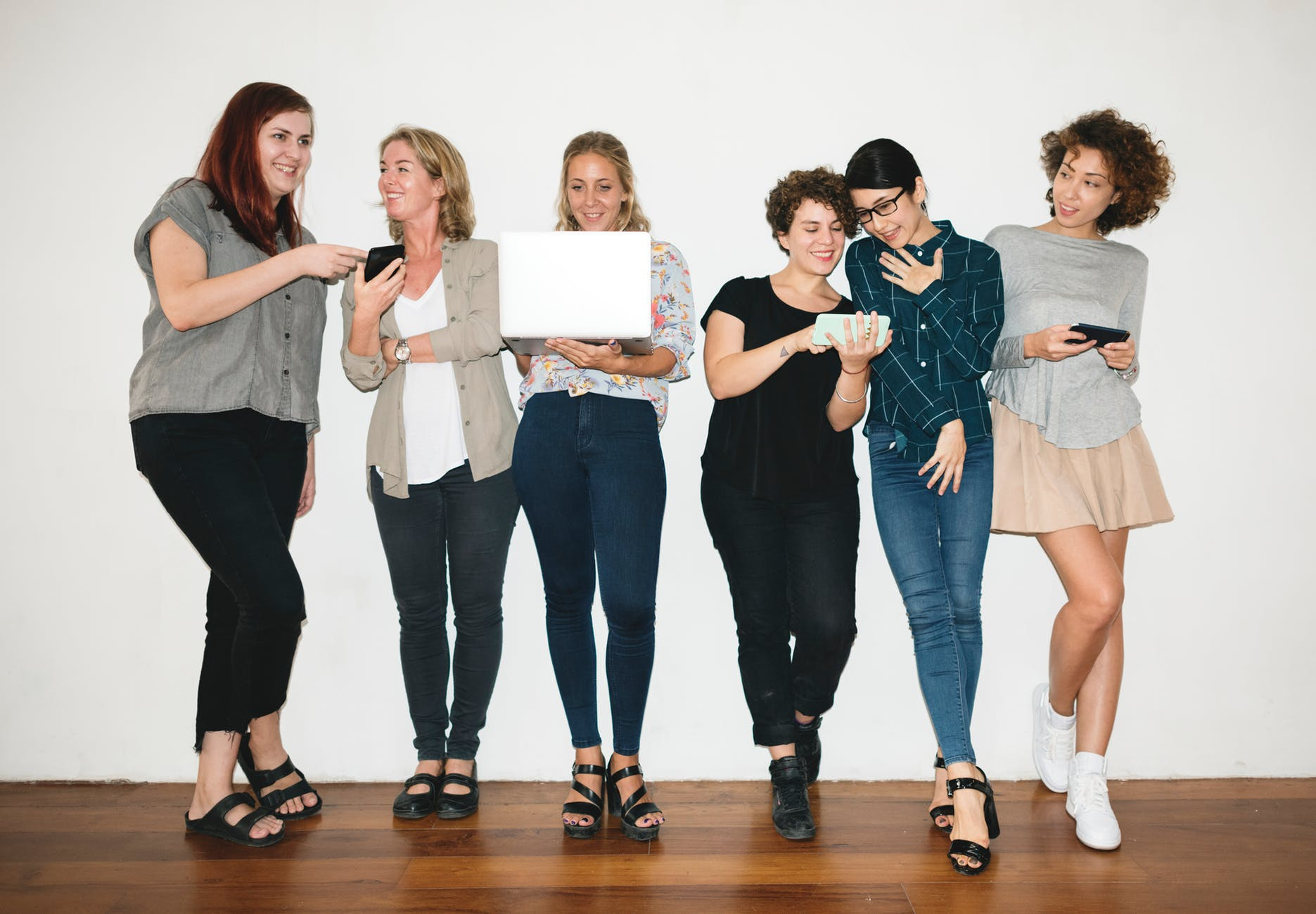 woman holding white laptop between women